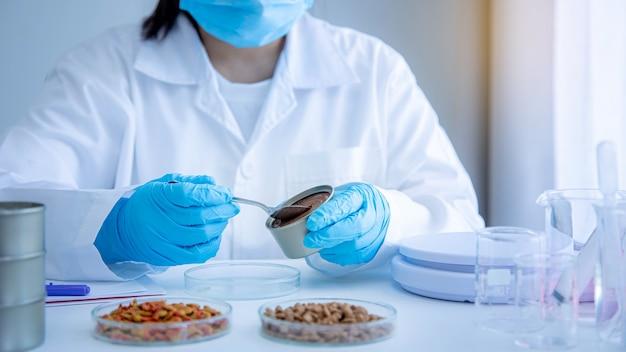 Kwaliteitscontrolepersoneel inspecteert de kwaliteit van natvoer voor huisdieren. tonijn kattenvoer in blik. kwaliteit van nat en droog voer voor huisdieren. kwaliteitscontroleproces in de huisdiervoedingsindustrie.
