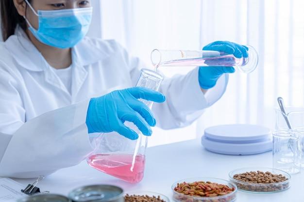 Kwaliteitscontrolepersoneel inspecteert het voer voor huisdieren van chemische kwaliteit. kwaliteit van nat en droog voer voor huisdieren. kwaliteitscontroleproces en chemische analyse van de petfoodindustrie.