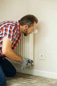 Kwaliteitshulpklusjesman die een waterpomptang gebruikt tijdens het repareren van de radiatorbatterij in de kamerverwarming