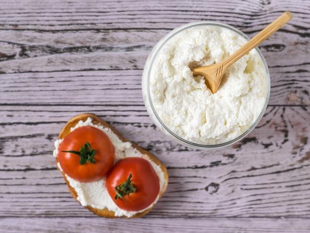 Kwark in een pot en brood met kwark en tomaten op een houten tafel. het concept van gezonde voeding. het uitzicht vanaf de top plat lag.