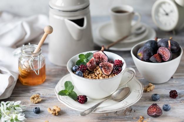 Kwark met vijgen, bessen, honing. kopje koffie en koffiepot. ontbijt. houten tafel.