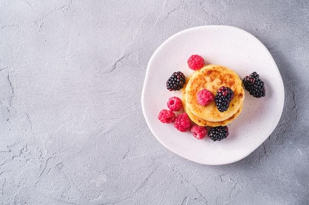 Kwark pannenkoeken, curd beignets dessert met frambozen en bramen bessen in plaat op stenen betonnen achtergrond,