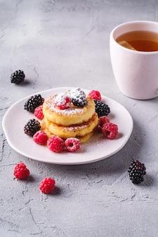 Kwark pannenkoeken en poedersuiker, kwark beignets dessert met frambozen en bramen bessen in plaat in de buurt van hete thee beker met schijfje citroen op stenen betonnen oppervlak, hoek bekeken