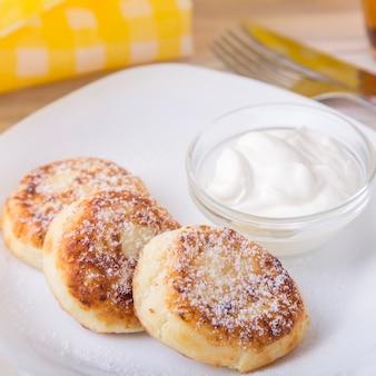 Kwark pannenkoeken met zure room en poedersuiker in een witte plaat.