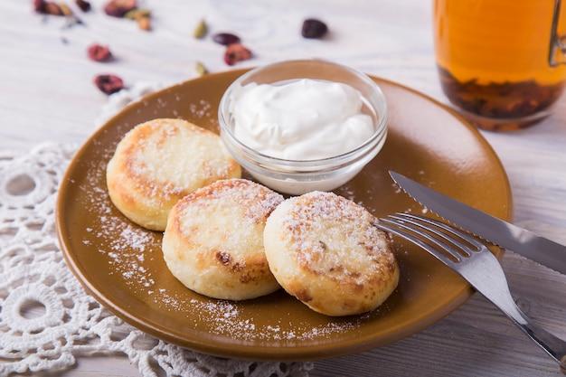 Kwark pannenkoeken met zure room en poedersuiker. zelfgemaakt gebak