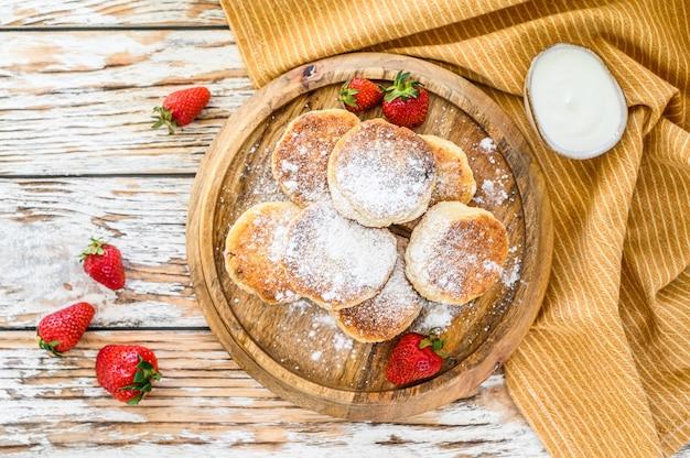 Kwark pannenkoeken, syrniki, kwarkbeignets met aardbei. gastronomisch ontbijt. bovenaanzicht