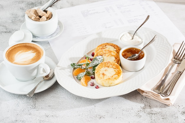 Kwark pannenkoeken, syrniki of cheesecakes met room, honing, munt geïsoleerd op wit textiel tafel. zelfgemaakt eten. lekker ontbijt. selectieve aandacht. hotizontal foto.