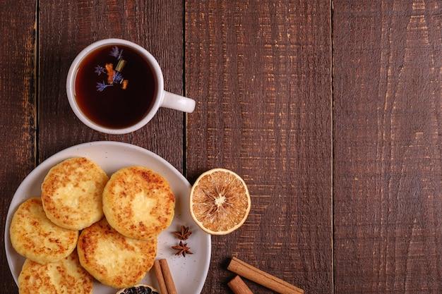 Kwarkbeignets met hete zwarte aromatische thee, kerstontbijtstemming met anijs, kaneel en gedroogde citrus op houten ondergrond, bovenaanzicht kopieerruimte