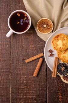 Kwarkbeignets met hete zwarte aromatische thee, kerstontbijtstemming met anijs, kaneel en gedroogde citrus op houten ondergrond, bovenaanzicht