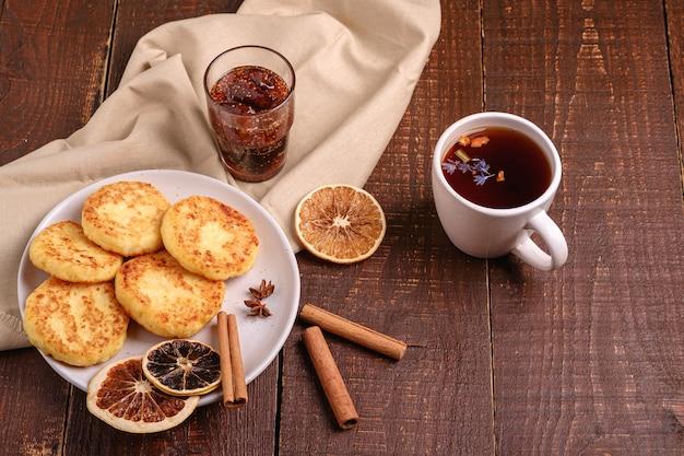 Kwarkbeignets met hete zwarte aromatische thee met vijgenjam, kerstontbijtstemming met anijs, kaneel en gedroogde citrus op houten ondergrond, hoekmening