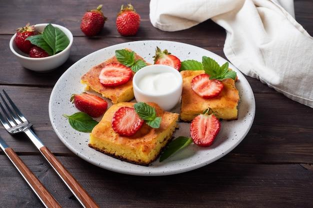 Kwarkbraadpan met aardbeien en munt. heerlijk huisgemaakt dessert gemaakt van wrongel en verse bessen met room. donkere houten achtergrond, kopieer ruimte.