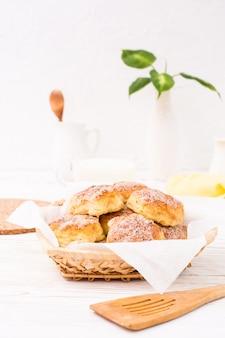 Kwarkkoekjes met suiker in een mand en een kop melk op een houten lijst worden bestrooid die