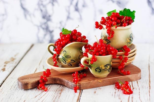 Kwarkkoekjesbroodjes met rode aalbessen op keramische plaat met vintage keramische thee of koffie set, theetijd, ontbijt, zomersnoepjes