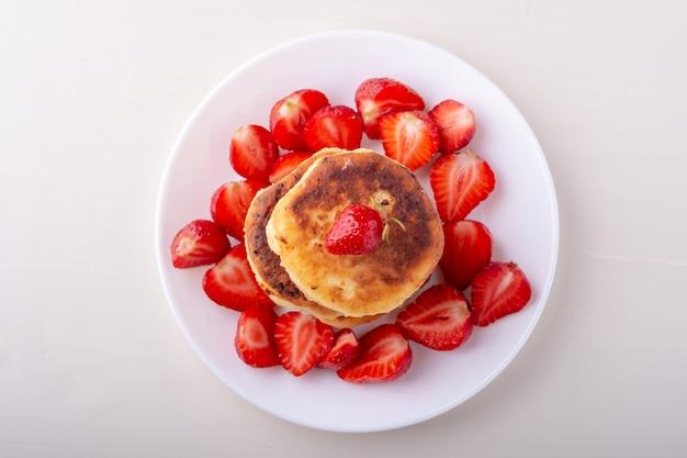 Kwarkpannekoeken met gesneden aardbeien op witte geïsoleerde plaat