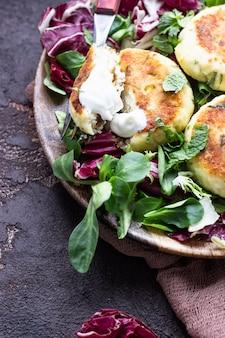 Kwarkpannenkoekjes met kaas en kruiden geserveerd met salademix en zure room.
