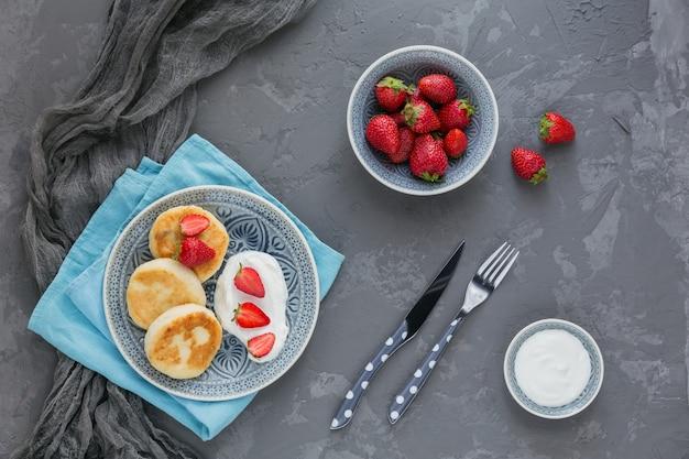 Kwarkpannenkoekjes met zure room en aardbeien voor ontbijt of lunch op grijs. bovenaanzicht Premium Foto