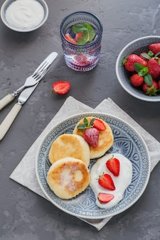 Kwarkpannenkoekjes met zure room en aardbeien voor ontbijt of lunch op grijs. Premium Foto