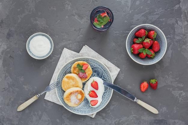 Kwarkpannenkoekjes met zure room en aardbeien voor ontbijt of lunch op grijs.