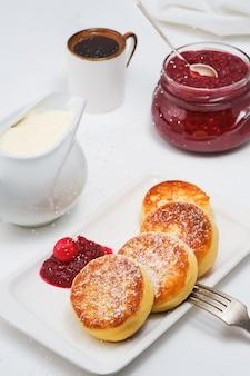 Kwarkpannenkoekjes of gebakken kwarkpannenkoekjes, bestrooid met poedersuiker, op een bord met cranberryjam en zure room.
