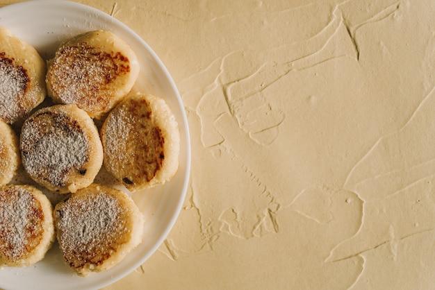Kwarkpannenkoekjes of syrniki met op keramisch bord heerlijk ontbijt of brunch