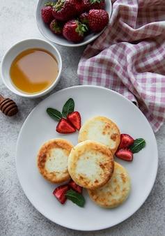Kwarkpannenkoekjes ricotta beignets op keramische plaat met verse aardbeien