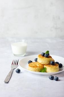Kwarkpannenkoekjes, syrniki, gestremde melk beignets met verse bosbessen en melk op lichte achtergrond. kopieer ruimte voor uw tekst.