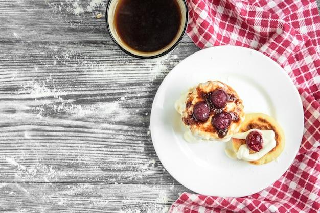Kwarkpannenkoekjes, syrniki, kwarkbeignets met verse bessen, framboos, aardbei, bosbes, blackberry en poedersuiker in een witte plaat. gastronomisch ontbijt. selectieve aandacht