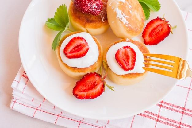 Kwarkpannenkoekjes, syrniki, wrongelbeignets met aardbei. gastronomisch ontbijt. witte achtergrond.