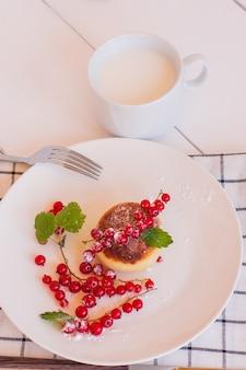 Kwarkpannenkoekjes, zoete wrongelbeignets met rode aalbessen, syrniki op ontbijttafel.