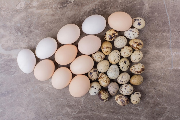 Kwartel en kippeneieren geïsoleerd op marmeren tafel.