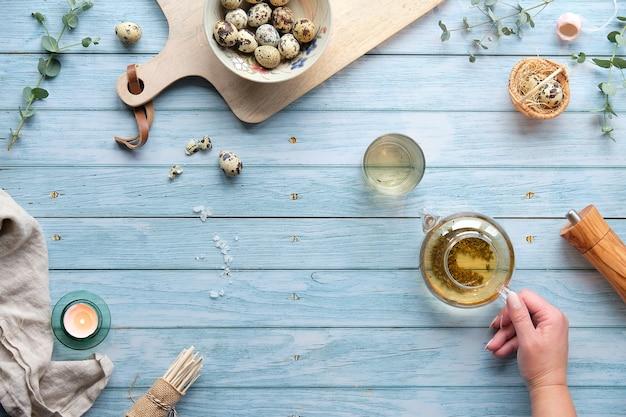 Kwartel paaseieren en natuurlijke lente decoraties, twijgen, eucalyptus. groene thee in glazen theepot.