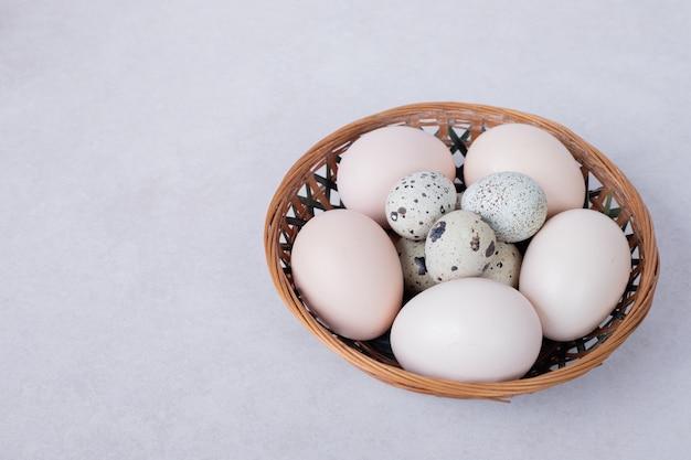 Kwarteleitjes en kippeneieren in kom op witte ondergrond.
