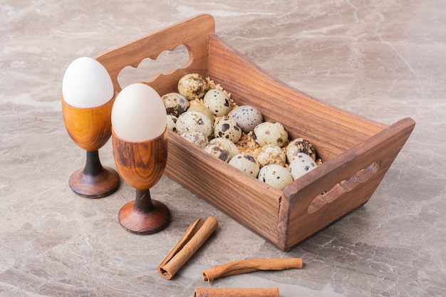 Kwarteleitjes in een houten bakje op stenen oppervlak