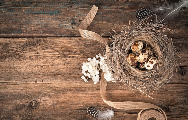 Kwarteleitjes in een natuurlijk vogelnest met bloemen en een lint op een houten achtergrond.