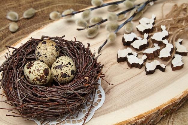 Kwarteleitjes in een nest, houten hazen en pussy-wilgentakken met toppen op een houten bord. pasen concept