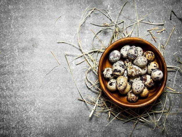 Kwarteleitjes in kom op hooi op stenen tafel.