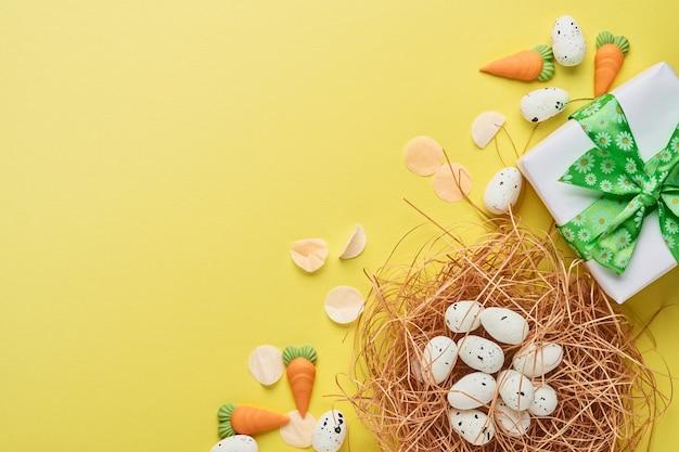 Kwarteleitjes in nest en geschenkdoos met groen lint op gele trendkleurentabel. pasen minimale creatieve horizontale compositie met kopie ruimte. lente happy easter kerstkaart. bovenaanzicht.