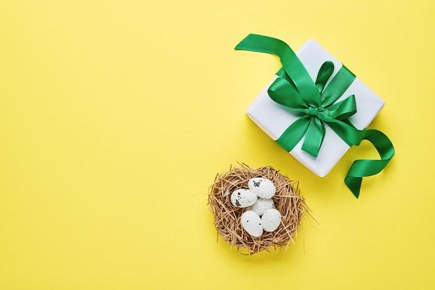 Kwarteleitjes in nest en geschenkdoos met groen lint op gele trendkleurentabel. pasen minimale creatieve horizontale compositie met kopie ruimte. lente vrolijk pasen. bovenaanzicht.
