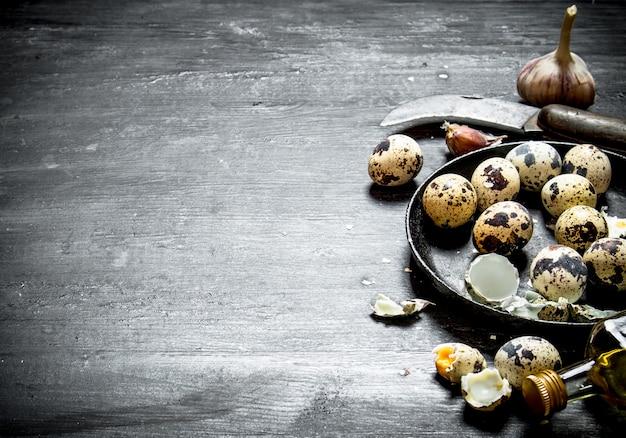 Kwarteleitjes met olijfolie en knoflook op zwarte houten tafel.