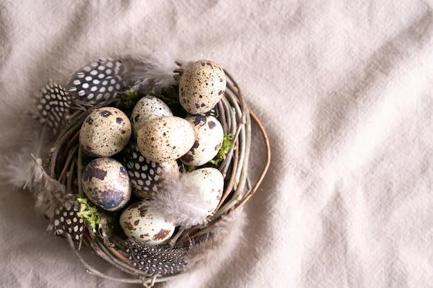 Kwartelpaaseieren en veer in vogelnest op natuurlijke linnen textielachtergrond met exemplaarruimte.