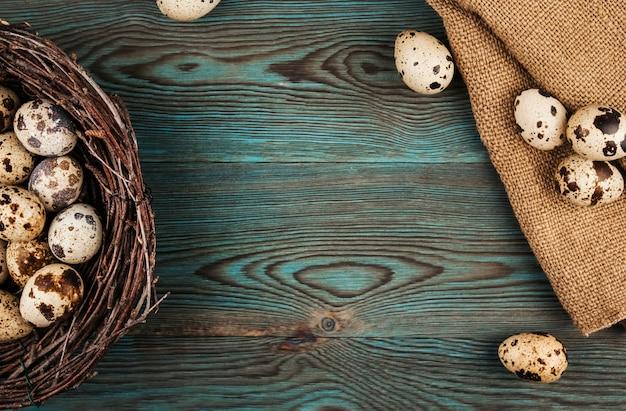 Kwartelseieren in een nest en jute op een blauwe houten achtergrondexemplaarruimte. natuurlijke pasen decoratie plat lag
