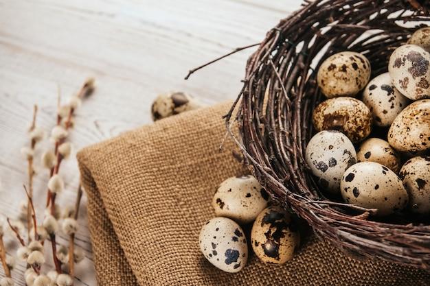 Kwartelseieren in een nest van berkentakken op jute. vogelnest. natuurlijke pasen decoratie