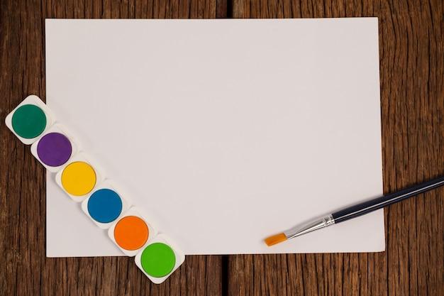 Kwast, aquarel palet en wit papier tegen witte achtergrond