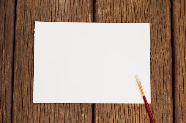 Kwast en wit papier op houten tafel