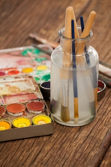 Kwast in een pot gevuld met water en aquarellen op houten tafel