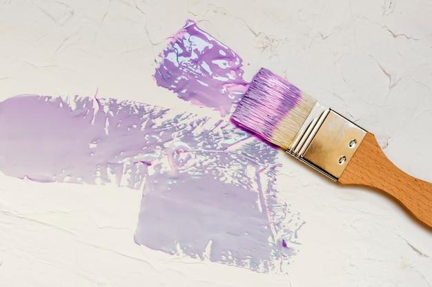 Kwast met kleur verf op witte muur achtergrond