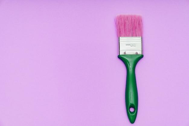 Kwast op een roze achtergrond. gereedschappen voor schilder- en reparatiewerkzaamheden.