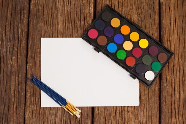 Kwasten, aquarel palet en wit papier tegen wit oppervlak