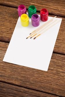 Kwasten, aquarelverf en wit papier op houten tafel
