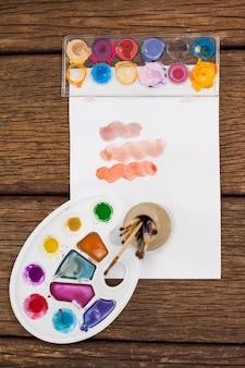 Kwasten, aquarelverf, glazen palet en wit papier op houten tafel